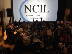 NCILのロゴマークの前で参加者で集合写真