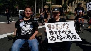 パレード用に「みんなかけがえのない存在」と書かれた大きな紙を持っている日本メンバー
