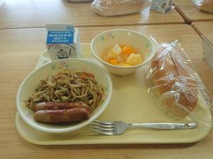 給食の写真。焼きそばにウィンナー2本、コッペパン、フルーツポンチに牛乳といった献立