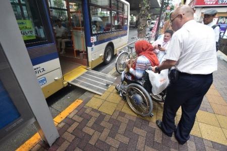 車いすユーザーがアクセシブルなバスのスロープに乗る様子
