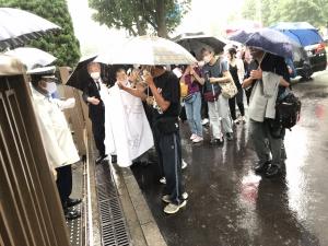 雨の中、入庁行動をとる原告・弁護団と支援者