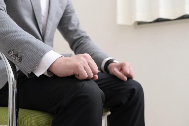 こぶしを握って座る男性