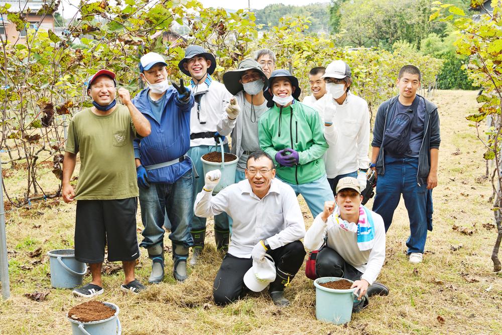 肥料牧作業中の皆さん。笑顔の集合写真