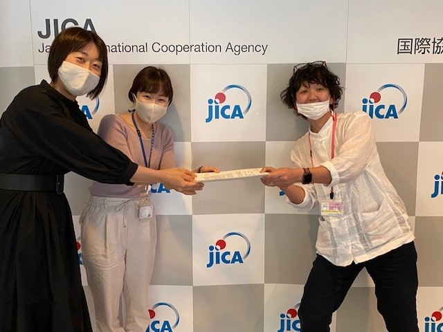 JICA東京にて。JICAと書いてある壁を背景に、廣瀬さんがJICA東京の担当スタッフ・小林様、篠崎様に契約書を手渡しているところ。