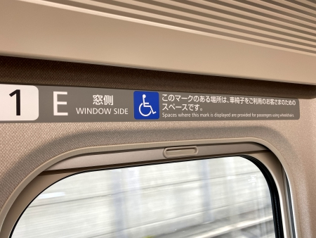 ▲写真:車椅子スペースには、窓枠付近に「このマークのある場所は、車椅子をご利用のお客さまのためのスペースです」と表示されています。