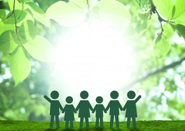 緑の中で手を繋ぎあう子どもたち